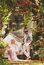boyfriend talking to girlfriend on a hammock in a green house