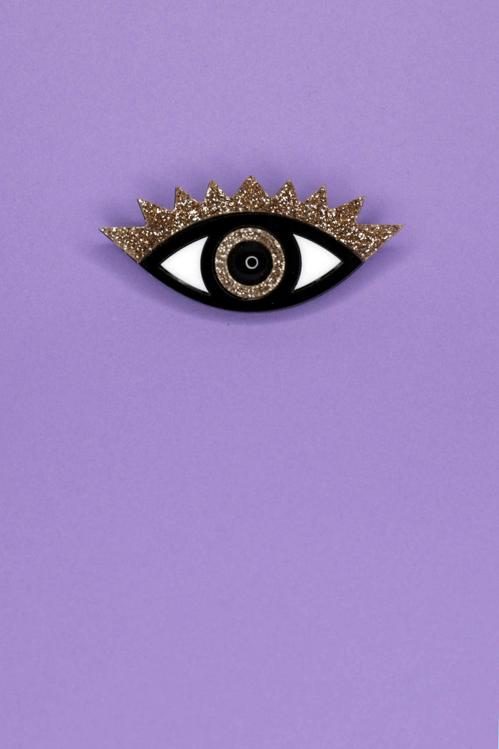 Layered laser cut Jennifer Loiselle acrylic pin with gold glitter, and a black onyx pupil