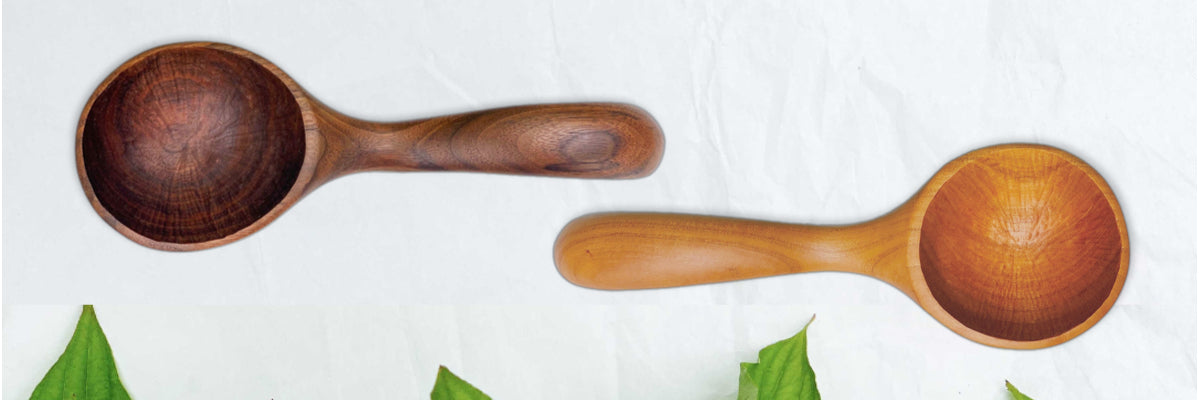 Two handmade large wood soup ladles made in the USA from black walnut and cherry woods on a table with green leaves