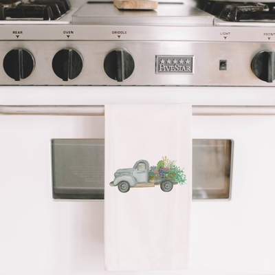 Picture of a dish towel with a watercolor painting of a truck with a bundle of flowering plants in the trunk | Made in New Jersey | LocalWe
