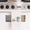 Picture of a dish towel with a watercolor painting of a brown bicycle carrying a bundle of flowering plants | Made in New Jersey | LocalWe