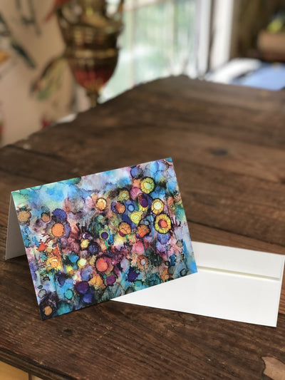 Photo of the Field of Flowers greeting card and white envelope showing a vibrant field of abstract flowers against a cool watercolor background. Card is propped up on a dark wood table.