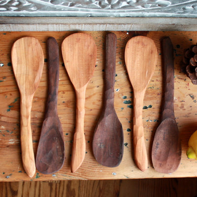 Arrangement of several charming rustic handmade wooden rice paddles made from cherry and black walnut urban wood