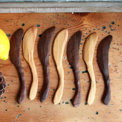 Arrangement of several charming rustic handmade wooden soft cheese spreader made from cherry and black walnut urban wood