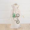 Photo of a tan wine bottle bag with a image of a brown bike carrying a green plan in the front basket | Made in New Jersey| LocalWe