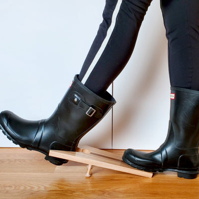 Stylish black boots being pulled off with a handmade hardwood boot jack