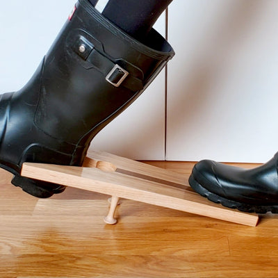 Close up of stylish black boots being pulled off with a handmade hardwood boot jack