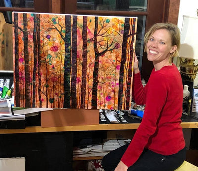 Artist sitting next to her painting of a colorful forest | Painted in NC | LocalWe