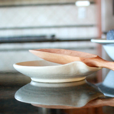 A side view of a farmhouse spoon rest handmade in Cambridge Wisconsin along with a cherry spoon.