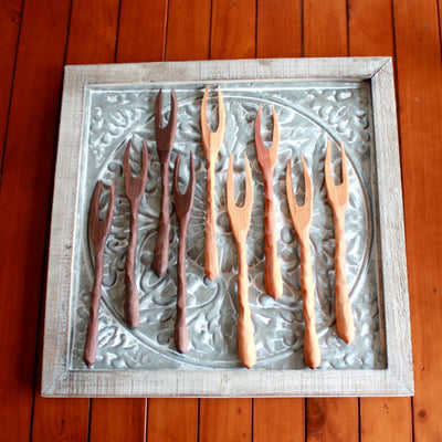 Several handmade wood meat forks in medium and dark wood resting on a vintage stamped metal decor background; hand-carved in Arkansas | LocalWe