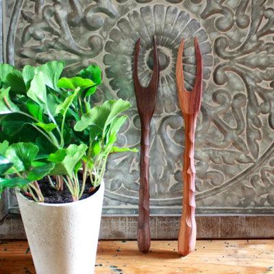 Two handmade wood meat forks in medium and dark wood resting on a vintage stamped metal decor background; hand-carved in Arkansas | LocalWe