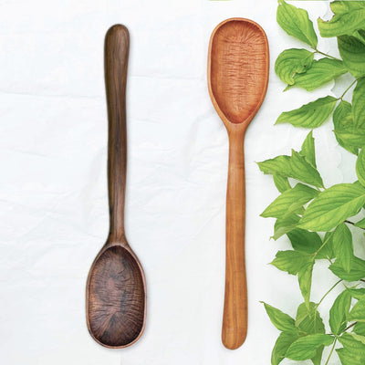 Two handmade large wood spoons in black walnut and cherry woods resting on a table with green leaves