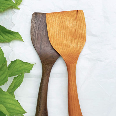 Two handmade long wood spatulas in black walnut and cherry woods on a table with green leaves