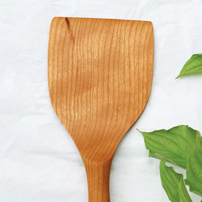 A handmade long wood spatula made from black walnut wood on a table with green leaves