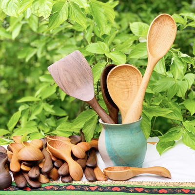 A turquoise jar filled with handmade wooden utensils outside against a green leafy background