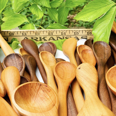 A collection of handmade wooden utensils outside on a table in front of a ruler and green leaves