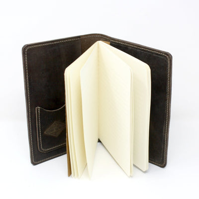 "Inside standing up view of a leather journal embossed with the inspirational quote ""Not All Those who Wander are Lost"" by J. R. R. Tolkien 