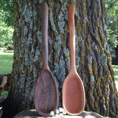 Two handmade large wood spoons in black walnut and cherry woods outside leaning up against a tree