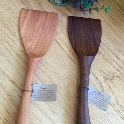 Two handmade long wood spatulas in black walnut and cherry woods resting on a wooden table