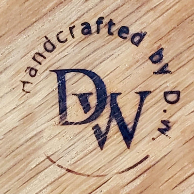 An Artisan woodworker's maker's mark that reads Handcrafted by DW