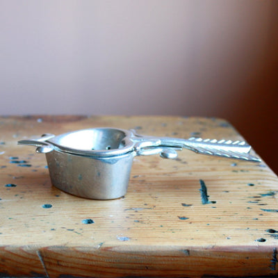 Side closed view of pewter tea strainer hand cast by artisans. Shop Local Rhode Island.