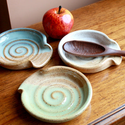 An arrangement of hand thrown pottery spoon rests with a wooden spoon and apple