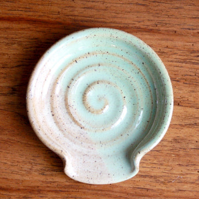 A hand thrown pottery spoon rest in Seagrass and Caramel color
