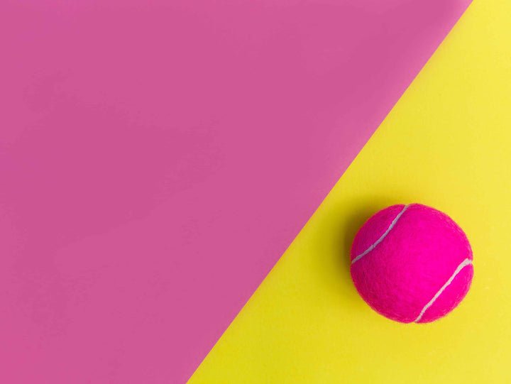 Bright pink tennis ball on yellow part of a pink and yellow background