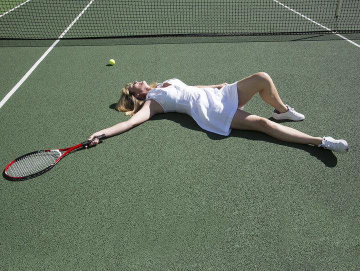 Woman lying on tennis court holding tennis racquet