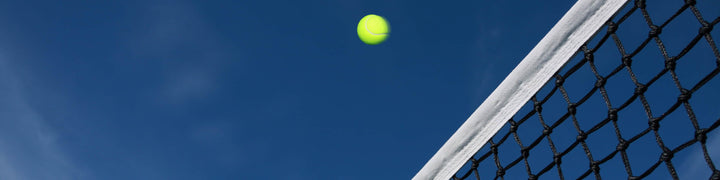 Tennis ball coming over the top of the net