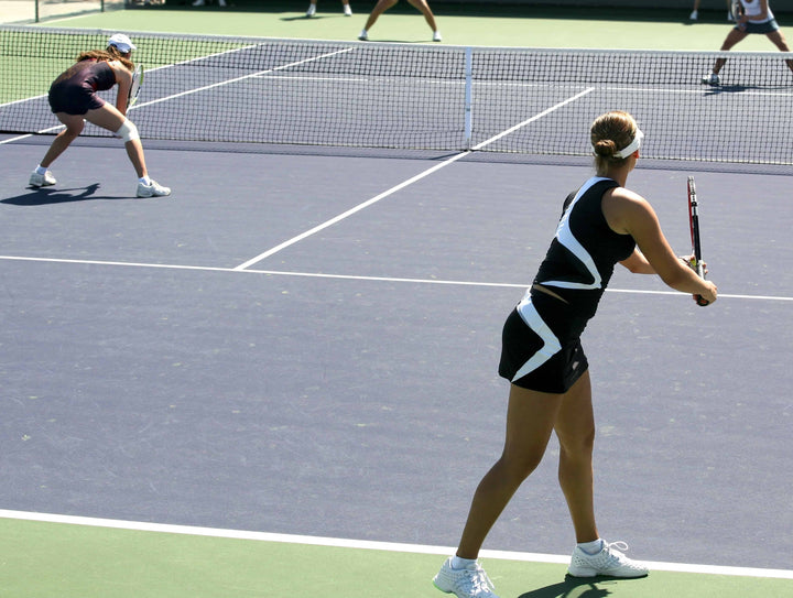 Competitive women's doubles team serving for the win
