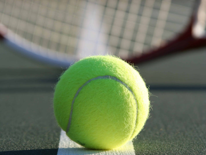 Closeup of tennis ball with racquet in background