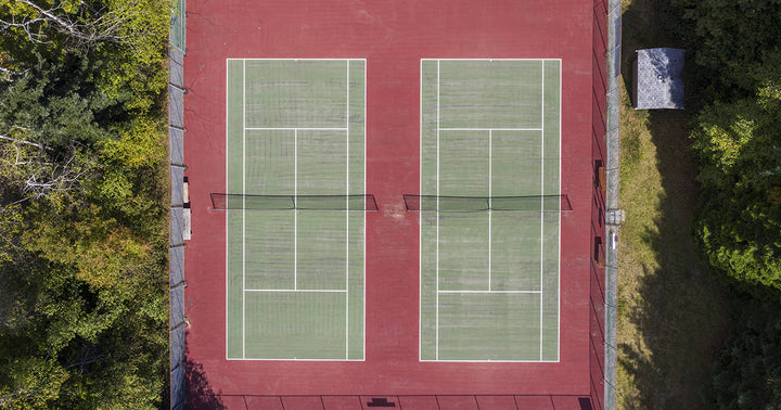 Ariel view of two tennis courts surrounded by trees