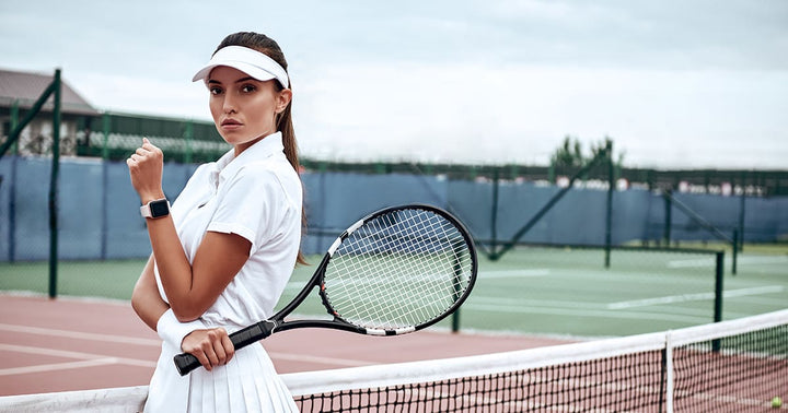 Woman with racquet and white visor stares intently at camera