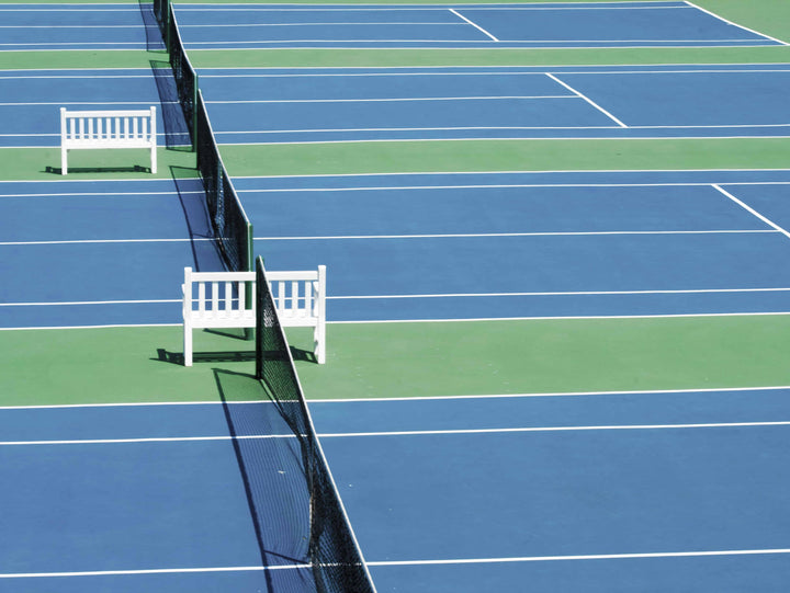Tennis courts with white benches in between