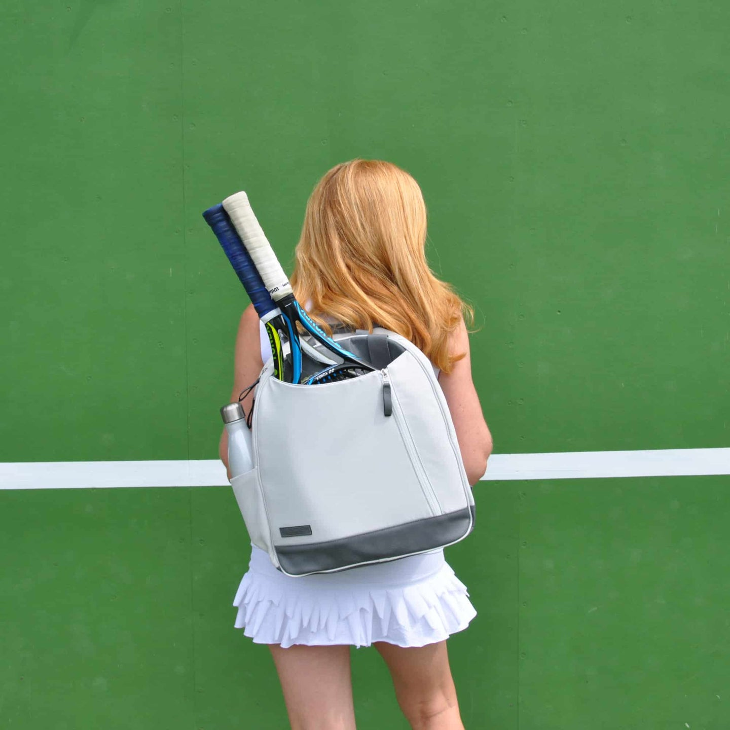 Woman in front of green wall with ivory and white Doubletake tennis backpack bag