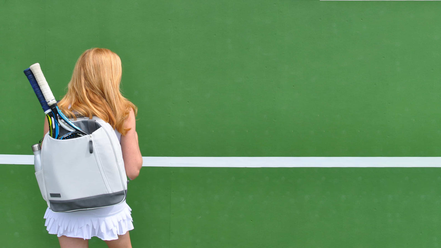 Woman with white Doubletake backpack against a bright green tennis hitting wall.
