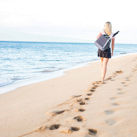 Woman walking on the beach with a navy and white Doubletake tennis backpack