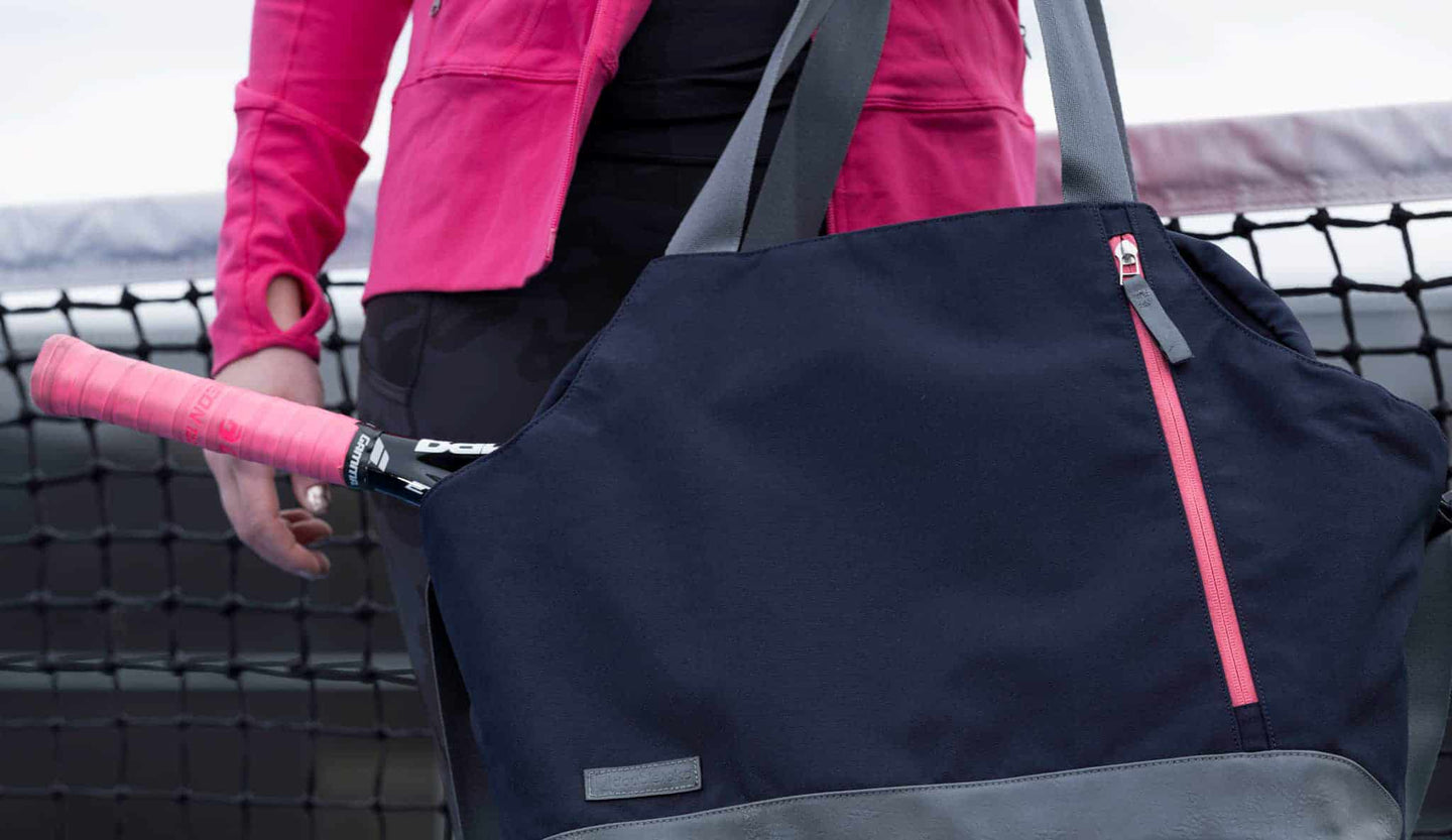 Woman in bright pink jacket holding a navy blue and bright pink doubletake tennis bag