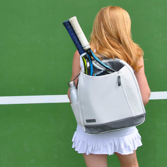 Woman carrying an ivory white Doubletake tennis backpack against a bright green background
