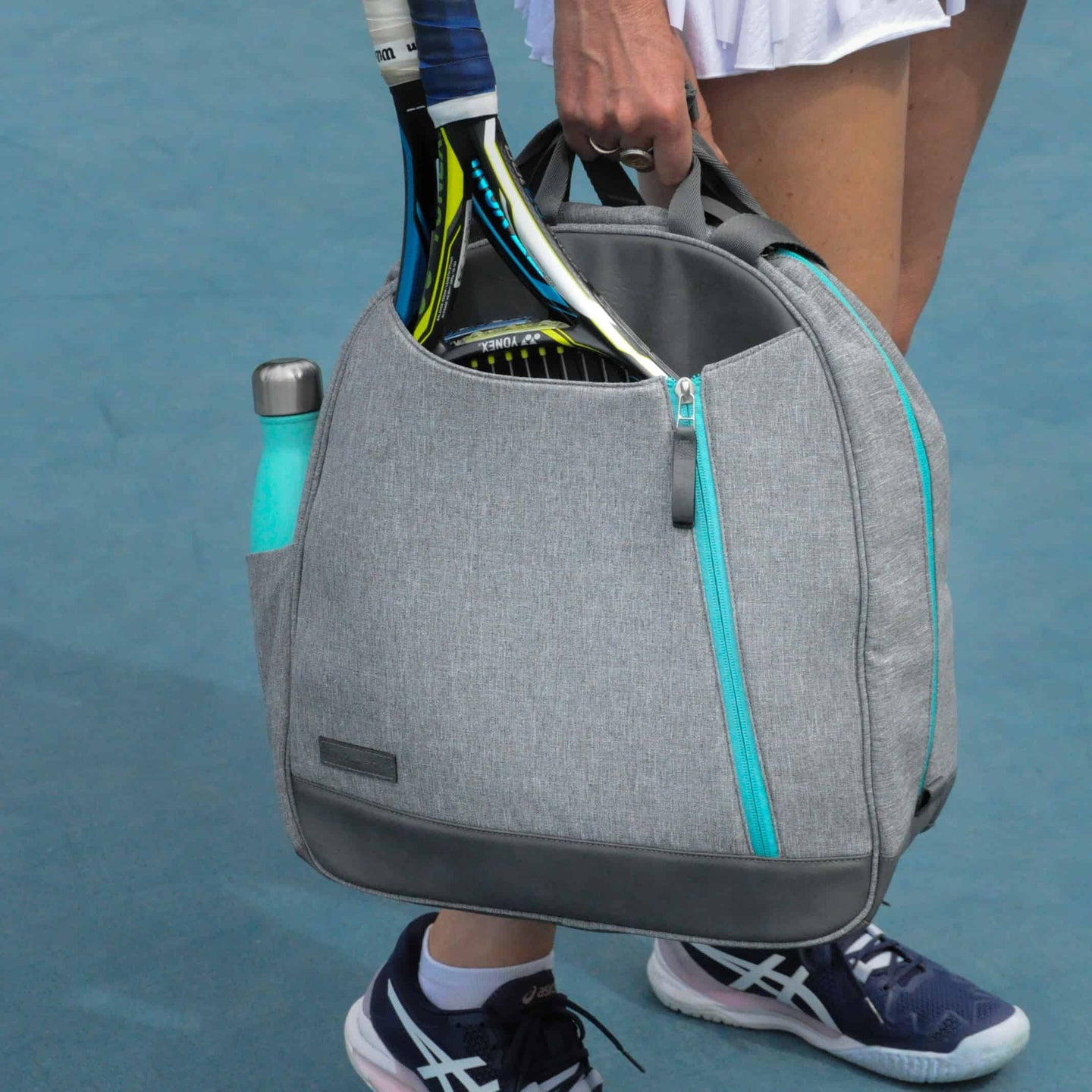 Woman on a tennis court carrying a heathered grey Doubletake backpack.