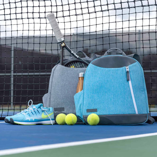 Doubletake turquoise blue tennis backpack in front of a heathered grey backpack on the tennis court