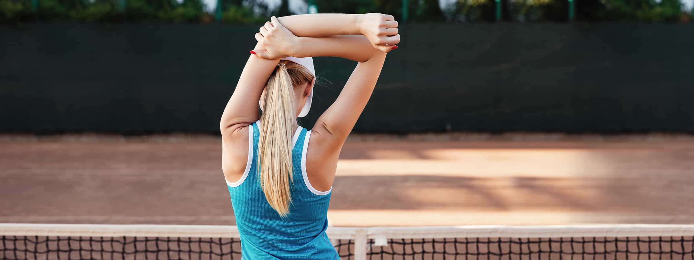 Woman stretching on a tennis court