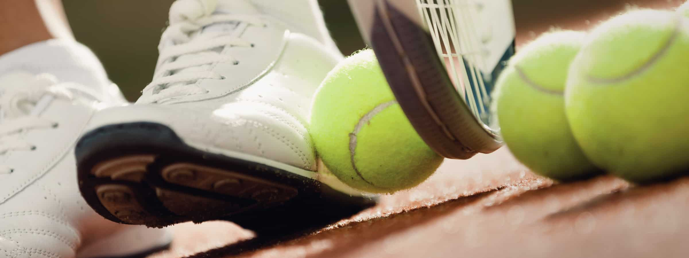 Person picking up tennis ball with shoe