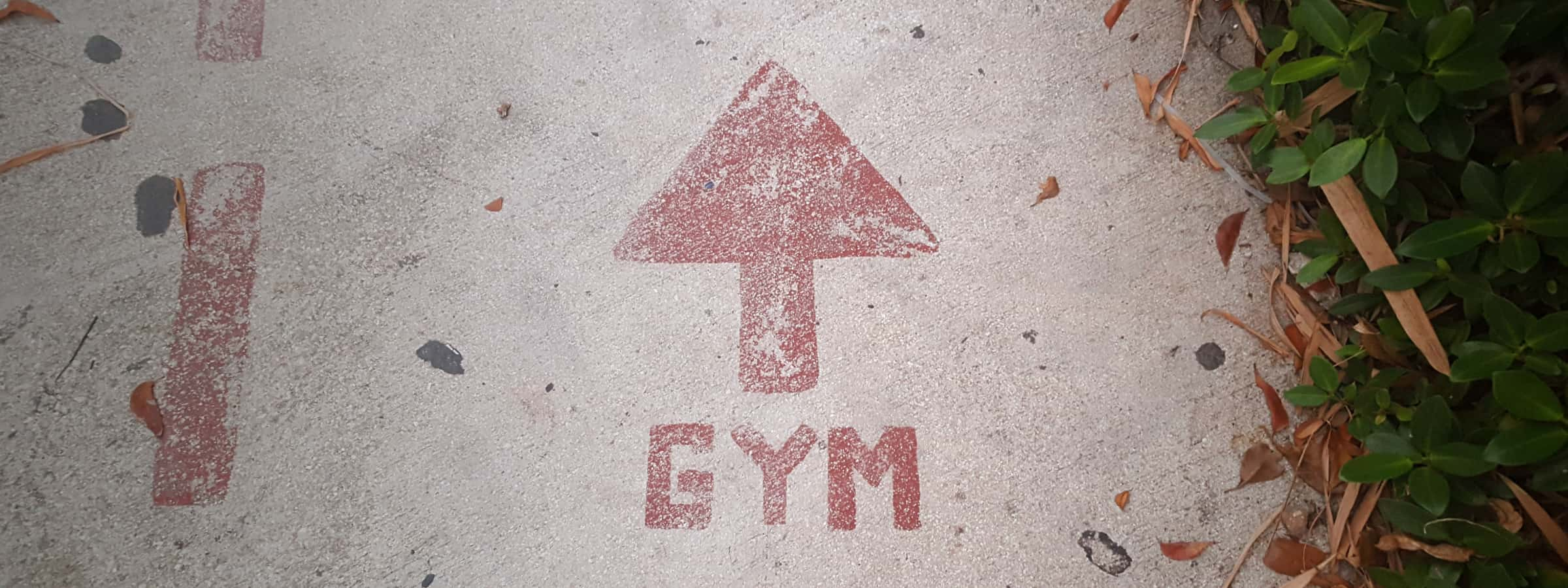 Cement floor with the word gym painted on it in red and an arrow
