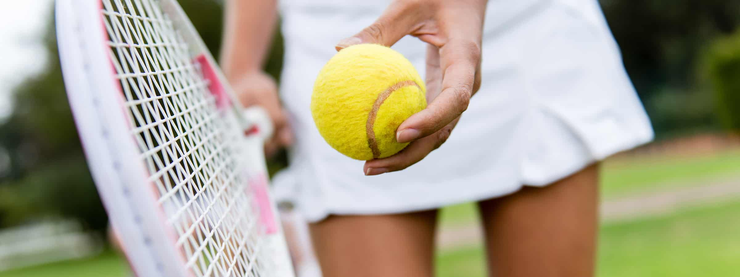 Woman holding tennis ball next to tennis racquet