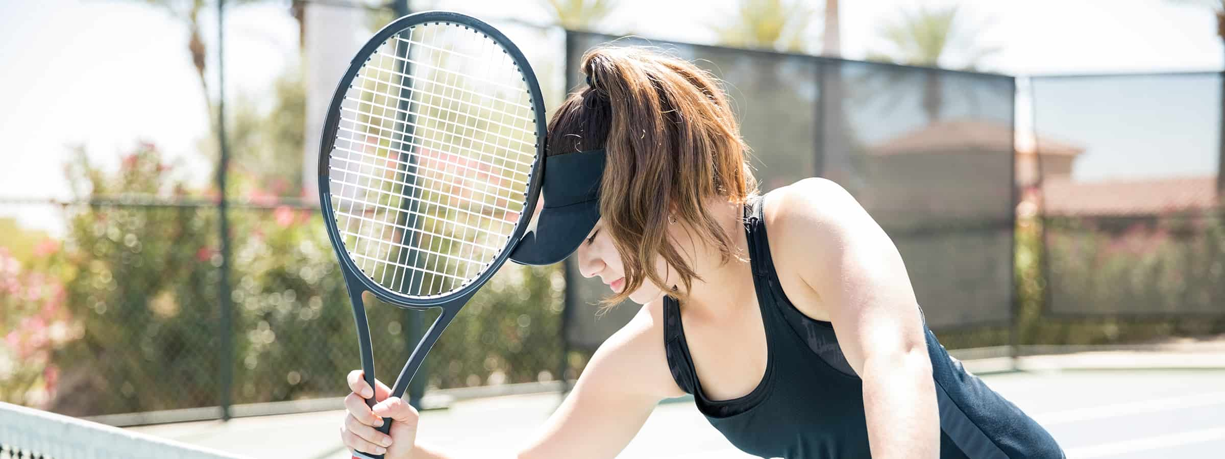 Woman hitting her head with the racquet