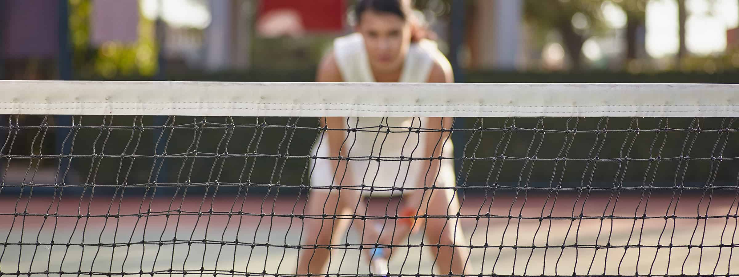 Woman in wide stance waiting for a volley to come over the net