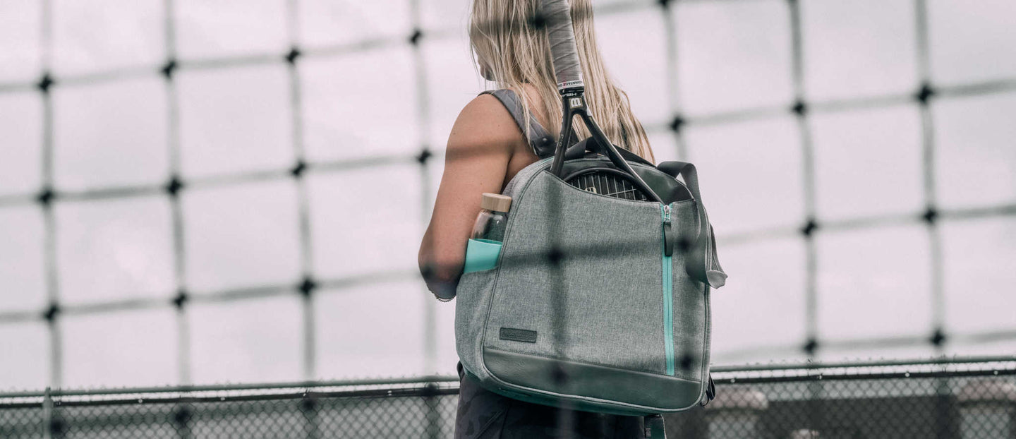 Woman standing with a grey and teal Melbourne backpack