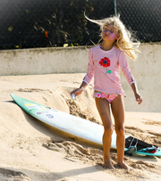 girl at the beach wearing sunuva poppy print rash vest